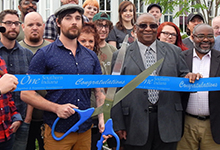 Man holds giant scissors and cuts ribbon.