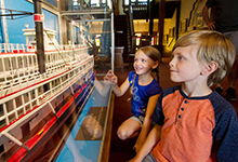 Children look at a ship in a museum.